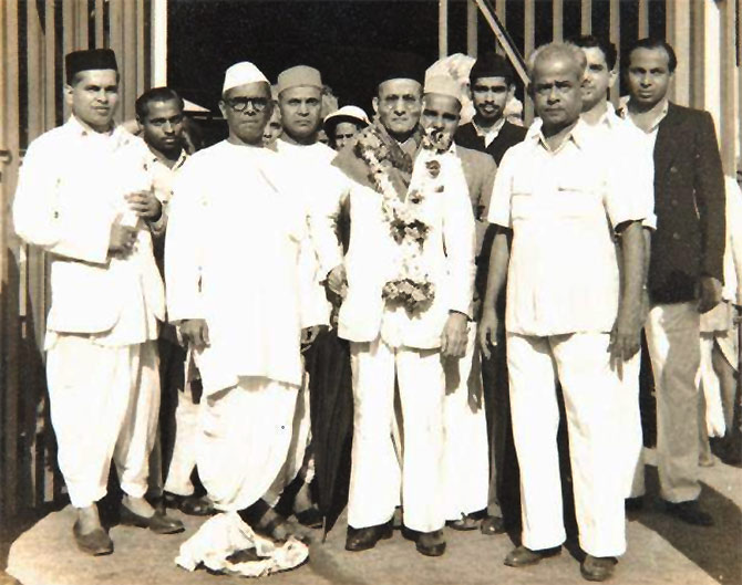 Savarkar, centre, with garland
