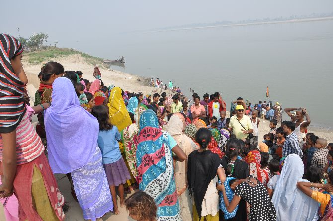 Team members speaking to villagers on the banks of the river