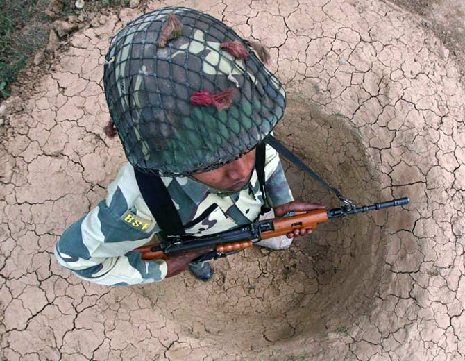 BSF soldier stands guard in a trench near Jammu