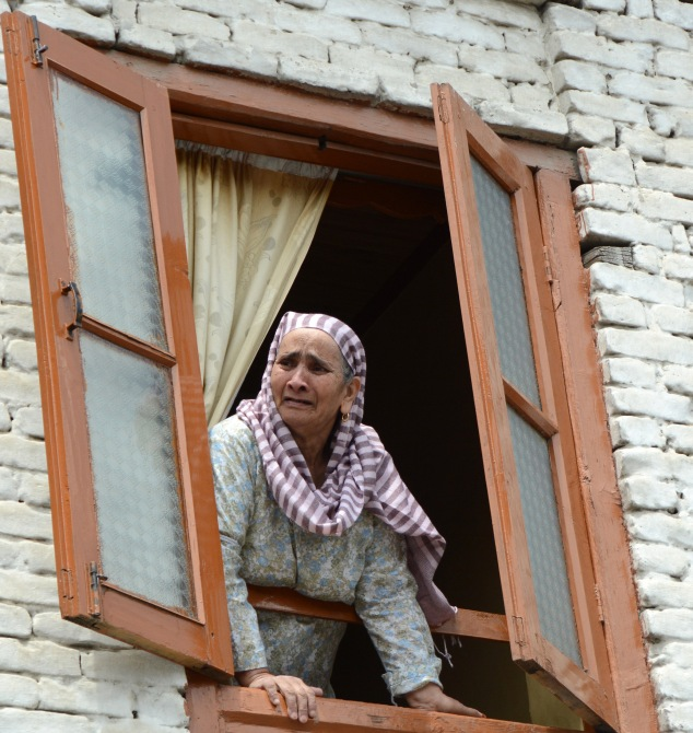 A woman looks out during street protests in Kashmir