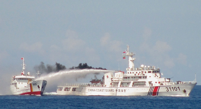 Chinese coast guard ship (right) uses a water cannon on a Vietnamese naval vessel near the disputed Paracel Islands in the South China Sea
