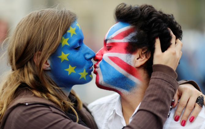 Two activists with the EU flag and Union Jack painted on their faces kiss each other in front of Brandenburg Gate to protest against the British exit from the European Union.