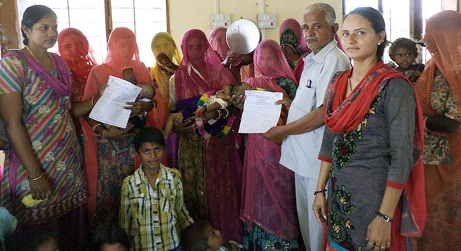 Birth certificates are handed over during a Balika Janamotsav in Jalore, Rajasthan