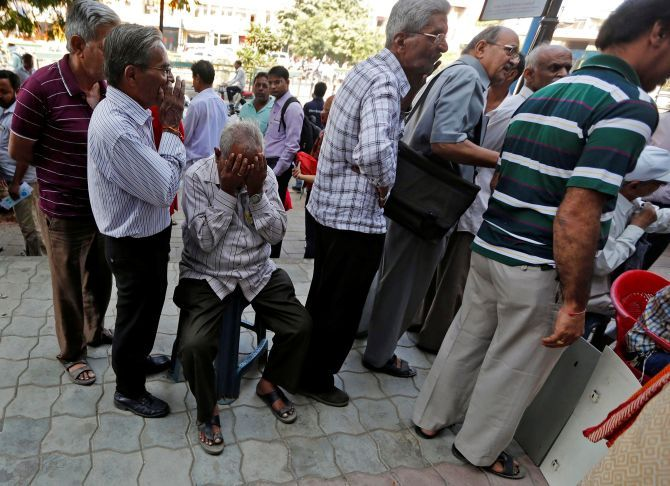 People wait to exchange old currency notes