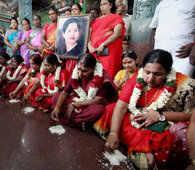 Members of the AIADMK women's wing eat food from the floor as a prayer for the speedy recovery of party supremo and Chief Minister J Jayalalithaa at a temple in Chennai. Photograph: PTI Photo