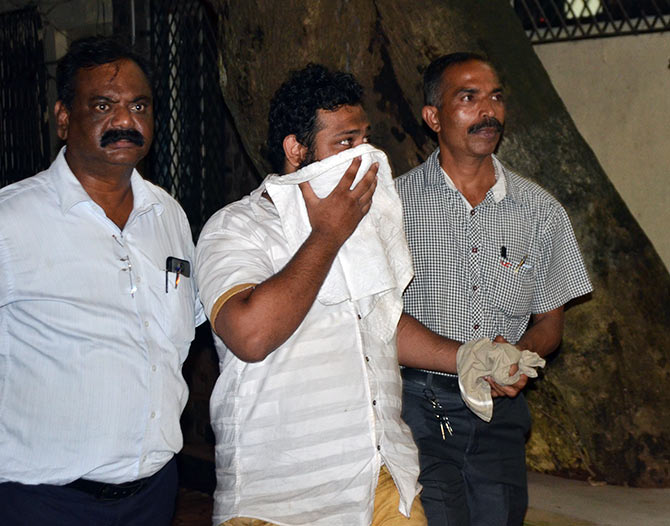 One of the 70 accused in police custody being taken for questioning at the Thane Crime Branch's Unit 1