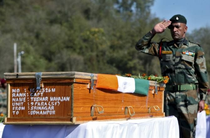 An Indian Army officer salutes at the coffin containing the body of Tushar Mahajan, an army officer who was killed in a gunbattle, in Udhampur, north of Jammu.