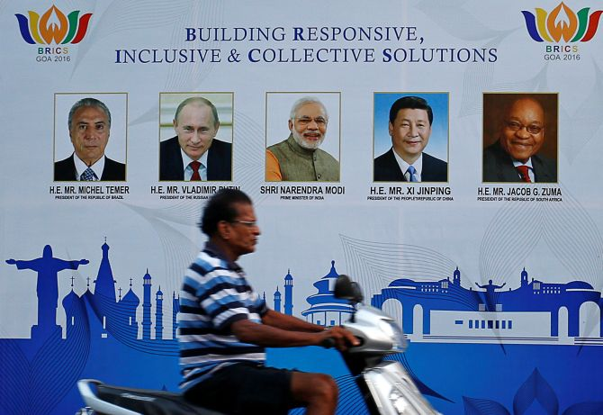 A man rides past a billboard near one of the venues of BRICS summit in Goa. Photograph: Danish Siddiqui/Reuters