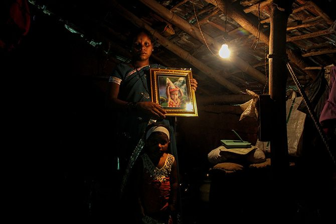Mamta Gurunath Savar holds a photograph of her daughter Roshni who died of malnutrition last year. Mamta and her other daughter Shalini live in Petranjani village, Mokhada taluka, Palghar district, Maharashtra in Mumbai's backyard. Photograph: Uttam Ghosh/Rediff.com