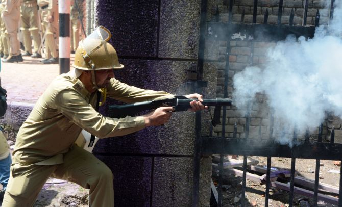 A J&K police personnel fires a tear gas shell