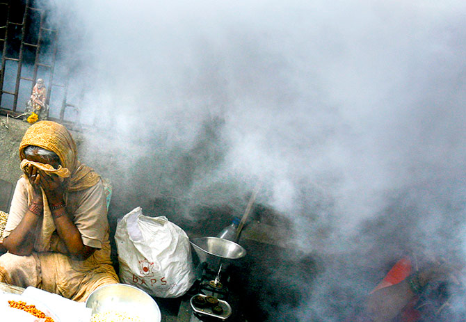 A street hawker covers her face during fumigation at a health drive by an Indian radio channel to create awareness about malaria in Mumbai July 25, 2007. Photo: Arko Dutta/Reuters