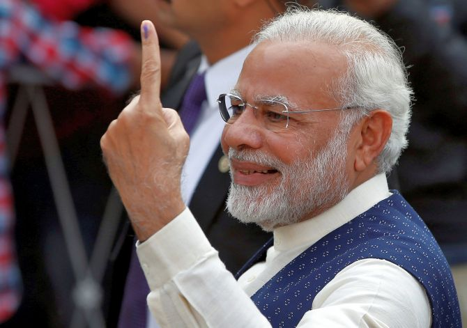 Modi votes in Gujarat, takes a walk with inked finger for crowds