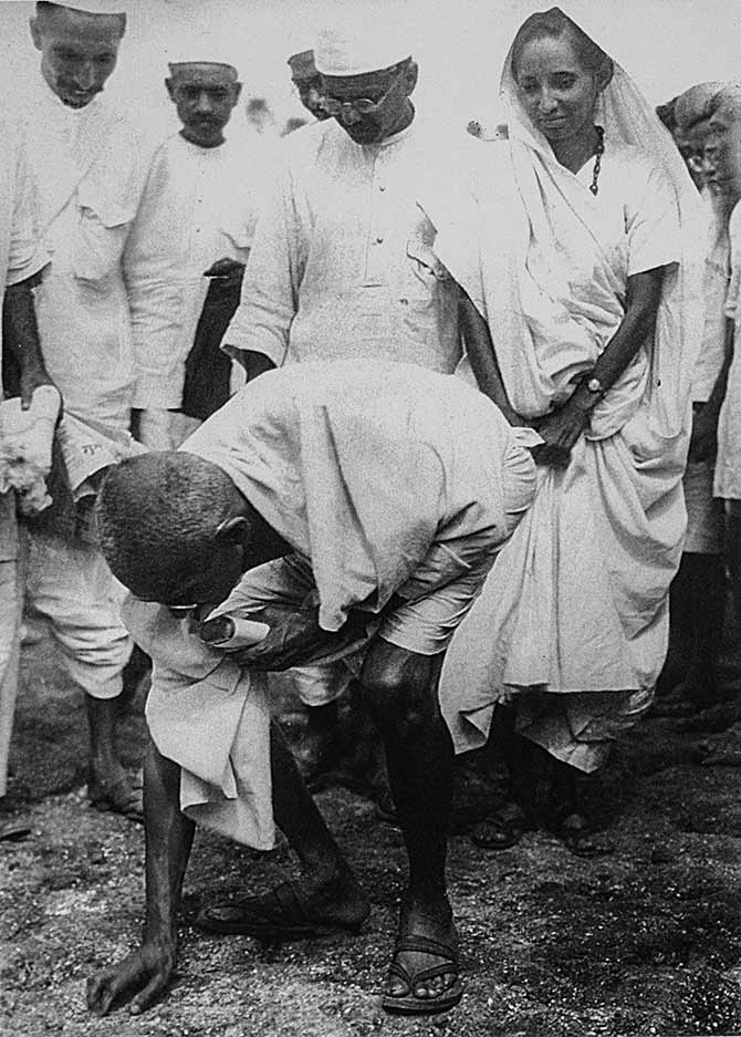 Mahatma Gandhi at Dandi, picking salt on the beach at the end of the salt march, April 5, 1930. Behind him is his second son Manilal