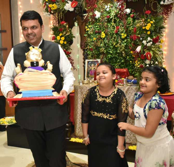 Maharashtra Chief Minister Devendra Fadnavis during Ganeshotsav with his daughter Divija (centre) and her friend on his way to Ganpati immersion at Girgaon Chowpaty