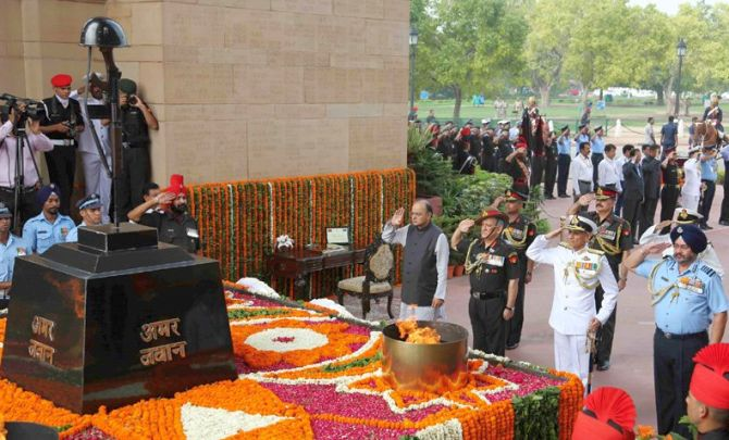 Then defence minister Arun Jaitley with the three service chiefs -- Army Chief General Bipin Rawat, Chief of the Naval Staff Admiral Sunil Lanba, and Air Chief Marshal Birender Singh Dhanoa -- pay homage to Kargil war heroes at the Amar Jawan Jyoti in New Delhi, July 26, 2017. Photograph: Press Information Bureau