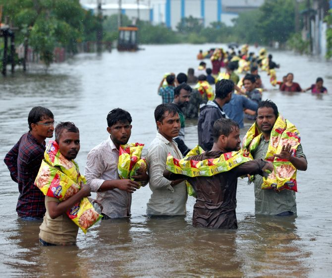 People carry packets of snacks handed out by volunteers in a flooded neighbourhood after heavy rains in Ahmedabad, July 2017. Photograph: Amit Dave/Reuters