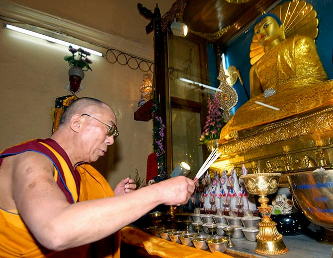 The Dalai Lama worships inside a monastery at Bodh Gaya.