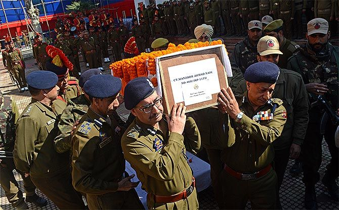 Jammu and Kashmir police officers carry the coffin of Constable Manzoor Ahmed Naik, a resident of Uri, who was killed in an encounter with Hizbul Mujahideen terrorist Aaquib Bhat and Pakistan terrorist Saif-ul-lah in Tral, south Kashmir, March 4/5, 2017. Naik took on the terrorists during the operation, which began at 7 pm on Saturday night and continued till 6.30 am. Photograph: Umar Ganie