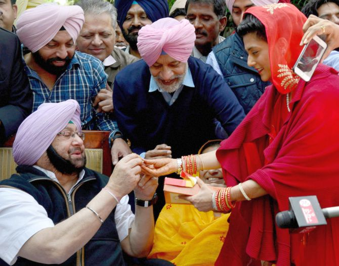 Captain Amarinder Singh is offered sweets by his grand daughter-in-law Mriganka Singh after his election victory. Photograph: PTI Photo