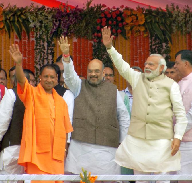 UP CM Yogi Adityanath, BJP president Amit Shah and PM Narendra Modi wave to the crowds after the swearing-in ceremony.