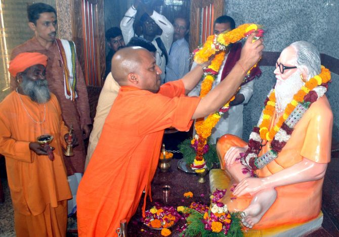 Uttar Pradesh Chief Minister Yogi Adityanath garlands his mentor Mahant Avaidyanath's statue in Gorakhpur. Photograph: PTI Photo