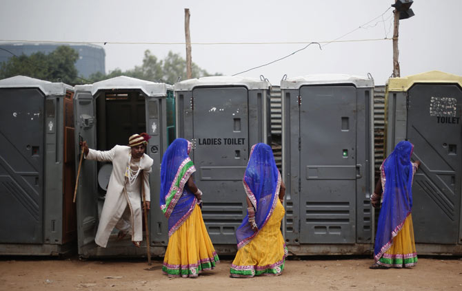 A groom emerges from a toilet, as brides stand outside the venue of a mass wedding ceremony, Ramlila grounds, New Delhi, June 15, 2014. Photo: Adnan Abidi/Reuters