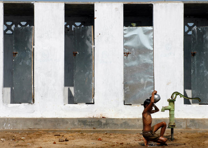 A boy takes bath outside newly-built toilets in a village on the outskirts of Nagapattinam, Tamil Nadu, December 24, 2005. Photo: Jagadeesh NV/Reuters