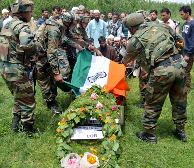 Army personnel pay tribute to slain army officer Lieutenant Ummer Fayyaz during his funeral at his native village Sudsona in Kulgam district. Photograph: PTI Photo
