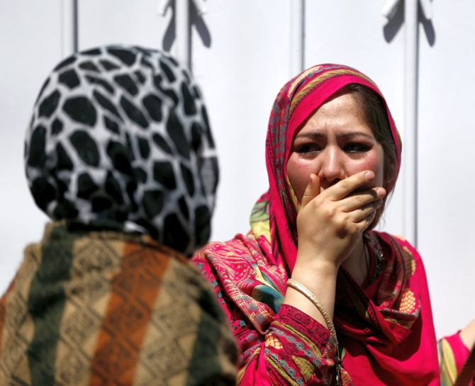 Relatives of Afghan victims mourn after the Kabul terror attack