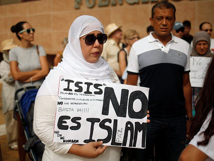A Muslim woman holds a sign that reads 'ISIS is not Islam' as she takes part in a gathering of Muslim, Christian and Jewish communities in Fuengirola, southern Spain, August 20, 2017, to protest the ISIS attack in Barcelona a few days earlier. Photograph: Jon Nazca/Reuters