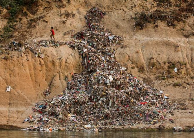 A boy runs past a pile of garbage along the river Ganges in Mirzapur, India, April 19, 2017. Photo: Danish Siddiqui/Reuters