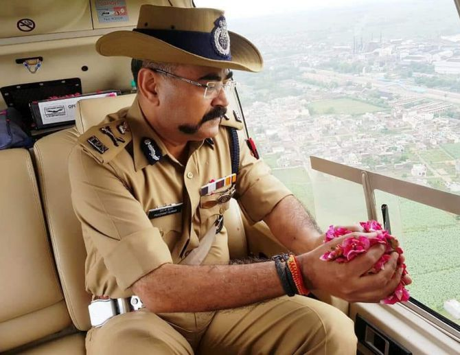 Uttar Pradesh's Additional Director General of Police - Meerut Zone Prashant Kumar showers rose petals on kanwariyas while on surveillance duty in a helicopter. Photograph: ANI