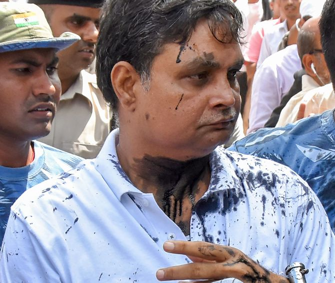 Brajesh Thakur, the main accused in the Muzaffarpur shelter home case, after a woman threw ink on his face while he was being taken to a special court in Muzaffarpur, August 8, 2018. Photograph: PTI Photo