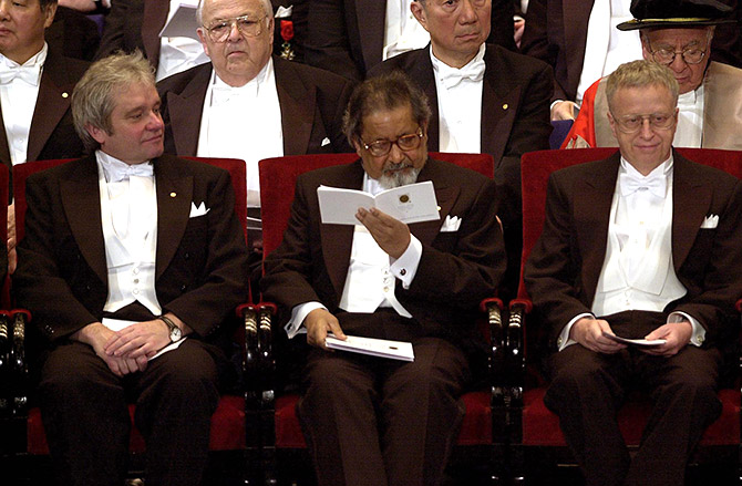 V S Naipaul looks at the programme for the Nobel Prize awards ceremony at the concert hall in Stockholm, December 10, 2001. Photograph: Leif R Janss/Reuters