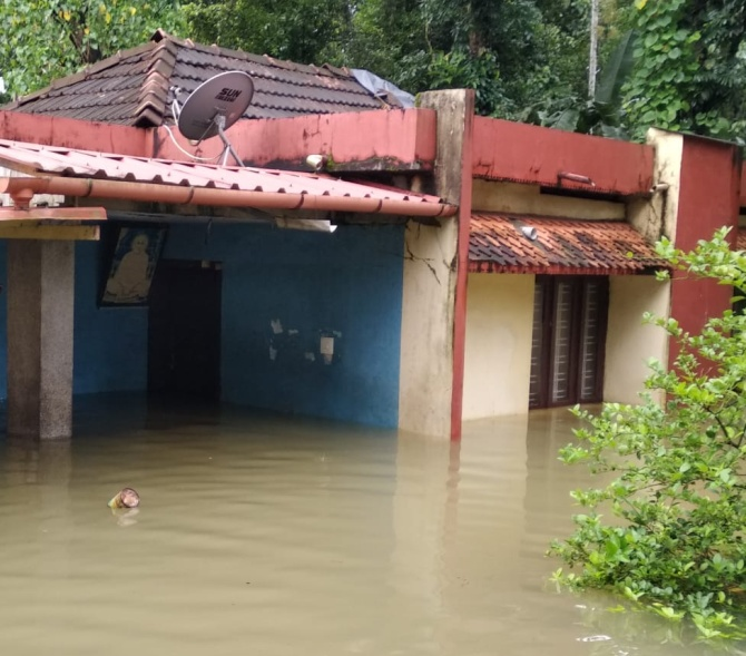 A portrait of Sree Narayana Guru watches over the flooded waters swirling through Prakash's home