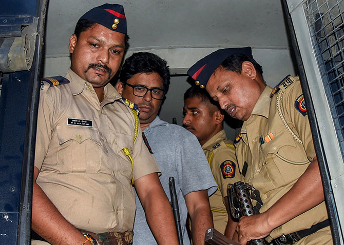 Social activist-lawyer Arun Ferreira is brought back to his home and placed under house arrest in Thane. Photograph: PTI Photo