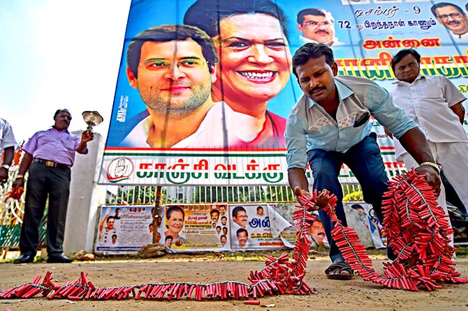 A Congress supporter lays down crackers to celebrate the party's performance in the assembly elections of Chhattisgarh, Madhya Pradesh and Rajasthan, whose results most exit polls <a href=https://www.rediff.com/news/report/most-exit-polls-failed-to-get-5-state-polls-right-rajasthan-madhya-pradesh-chhattisgarh-poll/20181212.htm target=new><strong>failed to predict</a></strong>. Photograph: PTI Photo