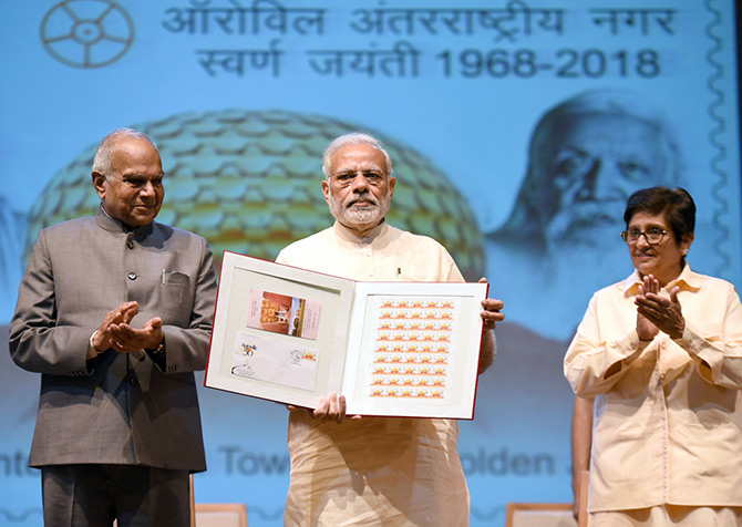 Prime Minister Narendra D Modi, flanked by Tamil Nadu Governor Banwarilal Purohit, left, and Puducherry Lieutenant Governor Kiran Bedi releases a stamp to honour Auroville at Auroville, February 25, 2018. Photograph: Press Information Bureau