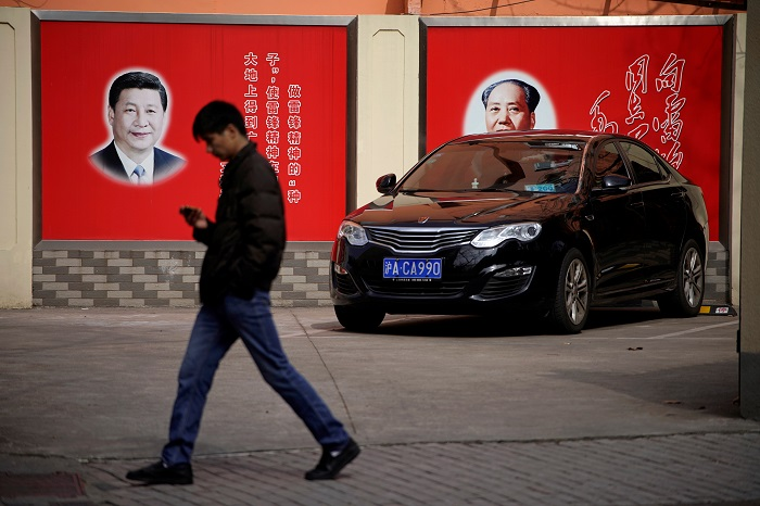 Portraits of Chinese President Xi Jinping and Mao Zedong overlook a street in Shanghai. Photograph: Aly Song/Reuters