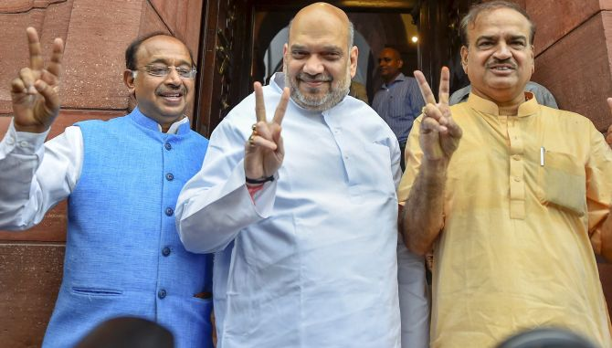 Bharatiya Janata Party national President Amit Anilchandra Shah, centrre, flanked by then parliamentary affairs minister Ananth Kumar, right, and Minister of State for Parliamentary Affairs Vijay Goel flash victory signs ahead of the no-confidence motion in the Lok Sabha, July 20, 2018. Photograph: Kamal Singh/PTI Photo