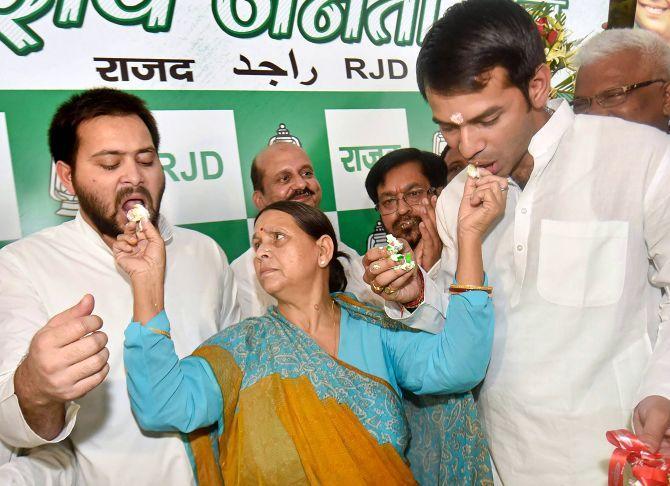 Former Bihar CM Rabri Devi feeds her sons Tejaswi Yadav, left, and Tej Partap Yadav, right, cake to celebrate her husband Lalu Prasad Yadav's 71st birthday in Patna, June 11, 2018. Photograph: PTI Photo