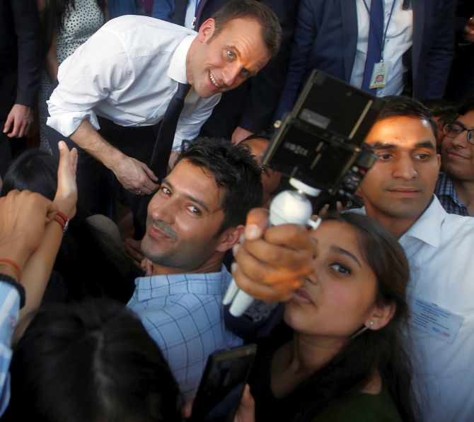 Students take a selfie with Macron, who turned 40 in December, at Delhi's Bikaner House. Photograph: Adnan Abidi/Reuters