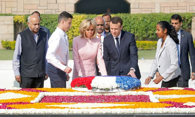 The Macrons pay their respects at the Mahatma Gandhi memorial at Rajghat. Photograph: Altaf Hussain/Reuters