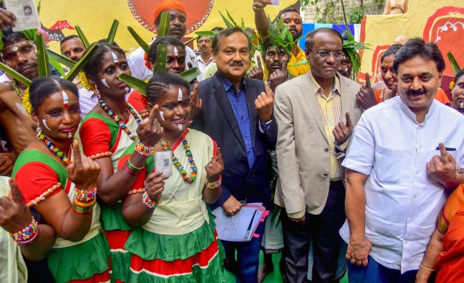 Karnataka Chief Electoral Officer Sanjiv Kumar with Siddi tribe members show their fingers marked with indelible ink during a voting awareness campaign ahead of the Karnataka assembly election in Bengaluru, May 10, 2018. Photograph: PTI Photo
