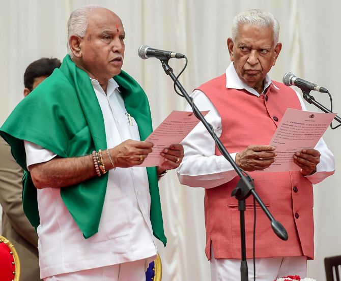 Karnataka Governor Vajubhai Vala, right, administers the oath of office to Bookanakere Siddalingappa Yeddyurappa as chief minister, May 17, 2018. Photograph: Shailendra Bhojak/PTI Photo