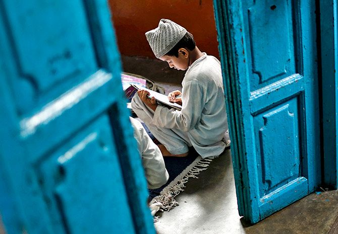 A young boy learning at a madrasa
