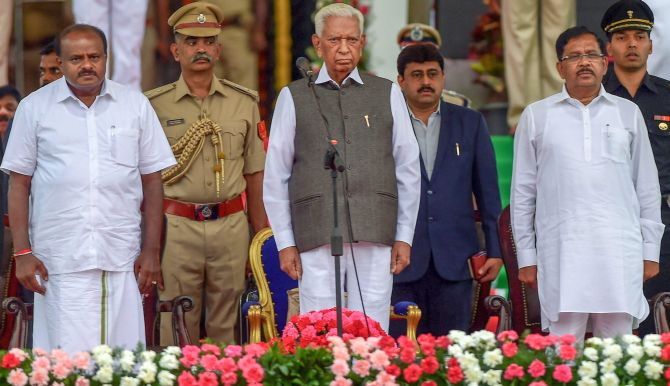 Karnataka Chief Minister H D Kumaraswamy, Governor Vajubhai Vala, Deputy Chief Minister G Parameshwara after the swearing-in ceremony, May 24, 2018. Photograph: Shailendra Bhojak/PTI Photo