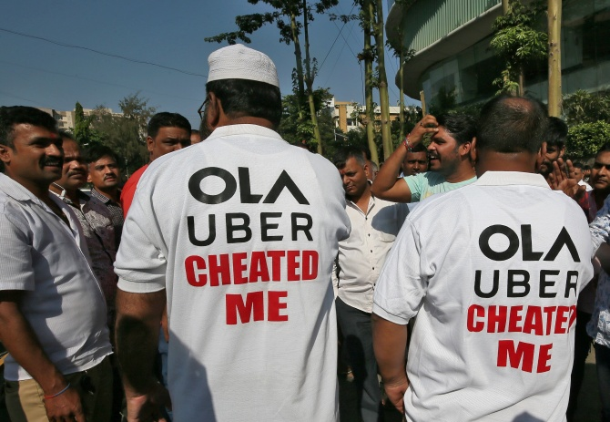 Drivers wear shirts with messages during a protest against Ola and Uber near Ola's office in Mumbai, India October 29, 2018.