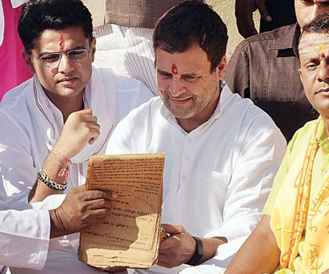 A pandit shows Rahul Gandhi a register containing his family's lineage at the Pushkar Sarovar, Pushkar, Rajasthan. Photograph: PTI Photo
