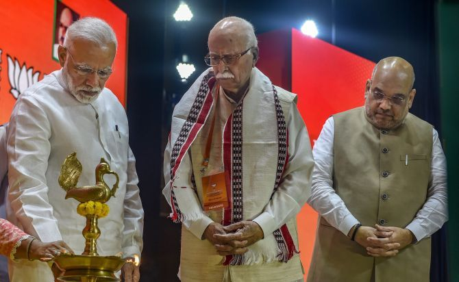Prime Minister Narendra Damodardas Modi lights a lamp as BJP President Amit Anilchandra Shah and party Margdarshak Mandal member Lal Kishenchand Advani look on before the BJP national executive meeting in New Delhi, September 8, 2018. Photograph: Atul Yadav/PTI Photo